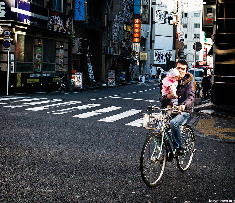 an irresponsible Japanese dad carrying his baby on a bike