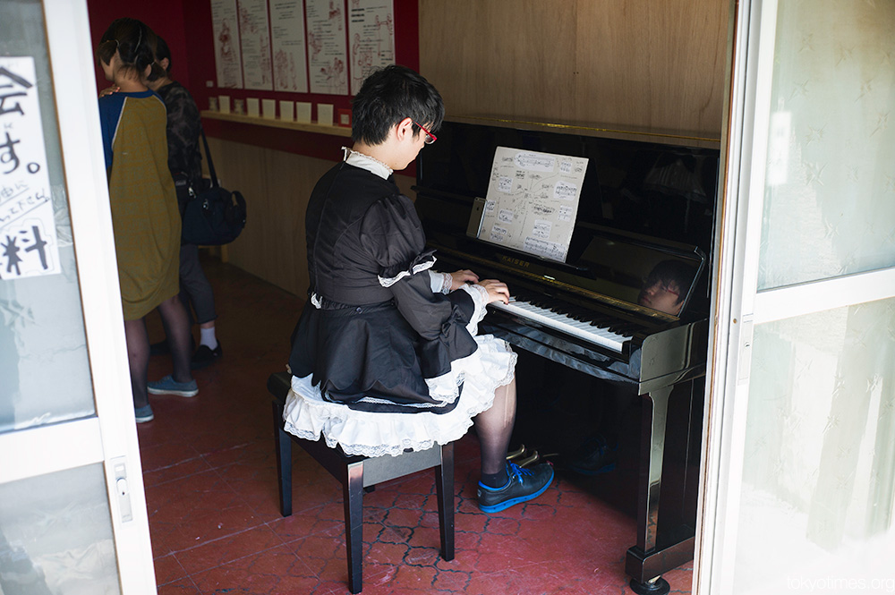Japanese man in a maid outfit playing the piano