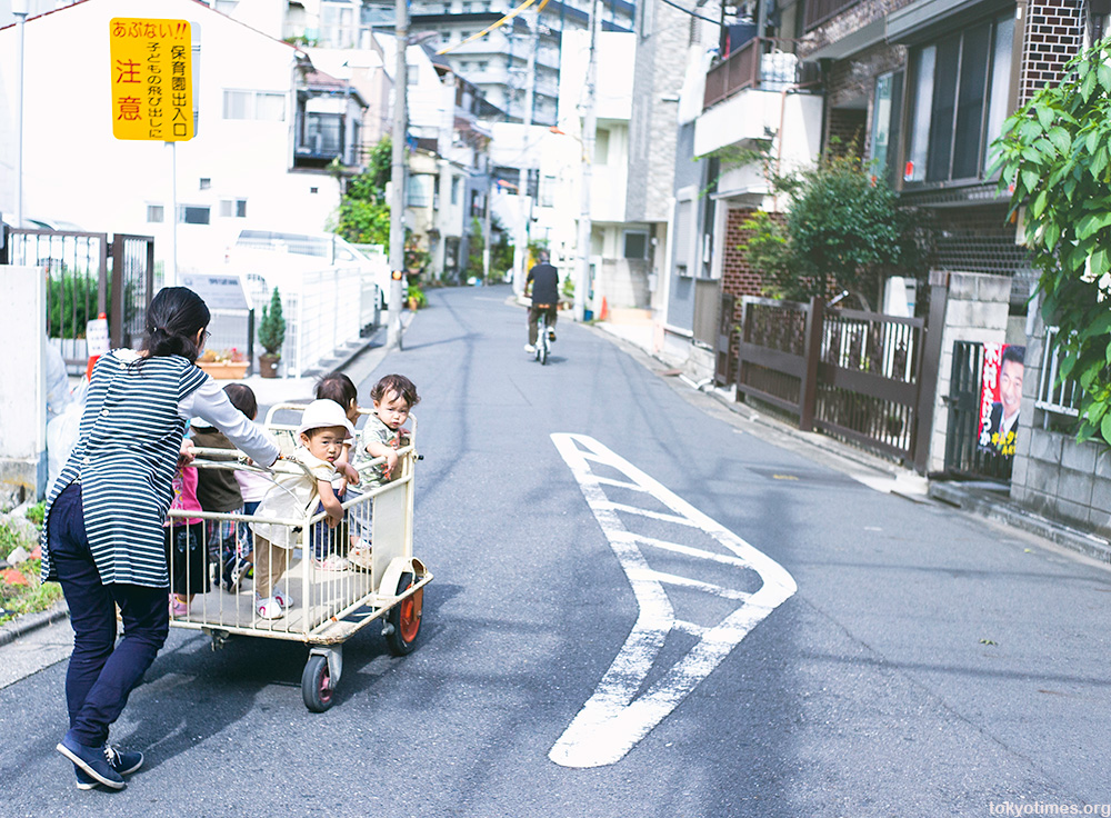 Japanese kids being pushed about in a cage or cart