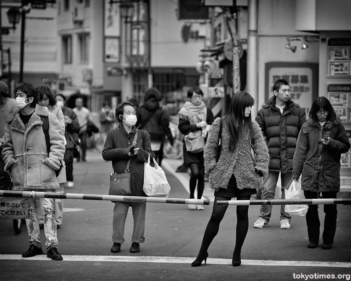 A beautiful Japanese woman at a level crossing