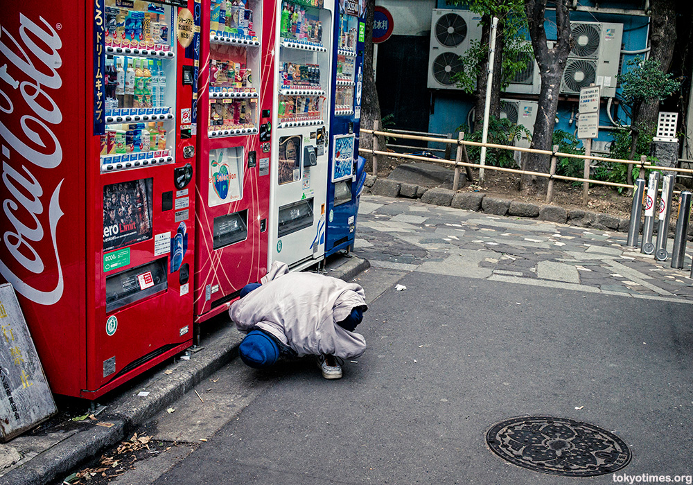 Japanese homeless man squatting and looking for money