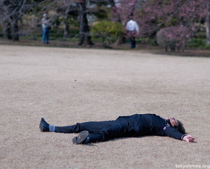 A  Japanese salaryman sunbathing in a suit