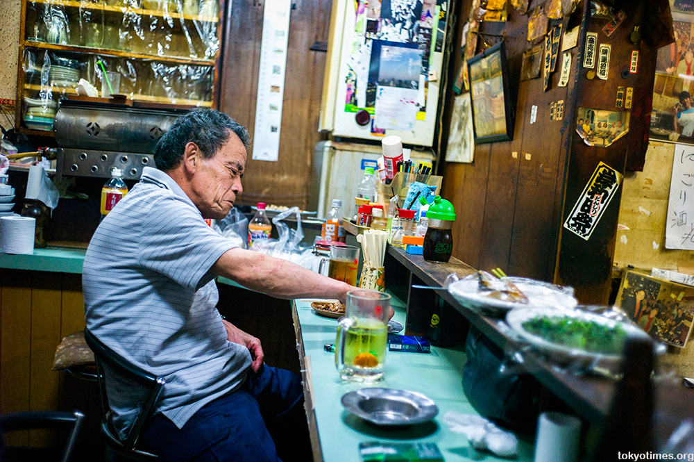 drinker in a tiny, dirty, Tokyo bar