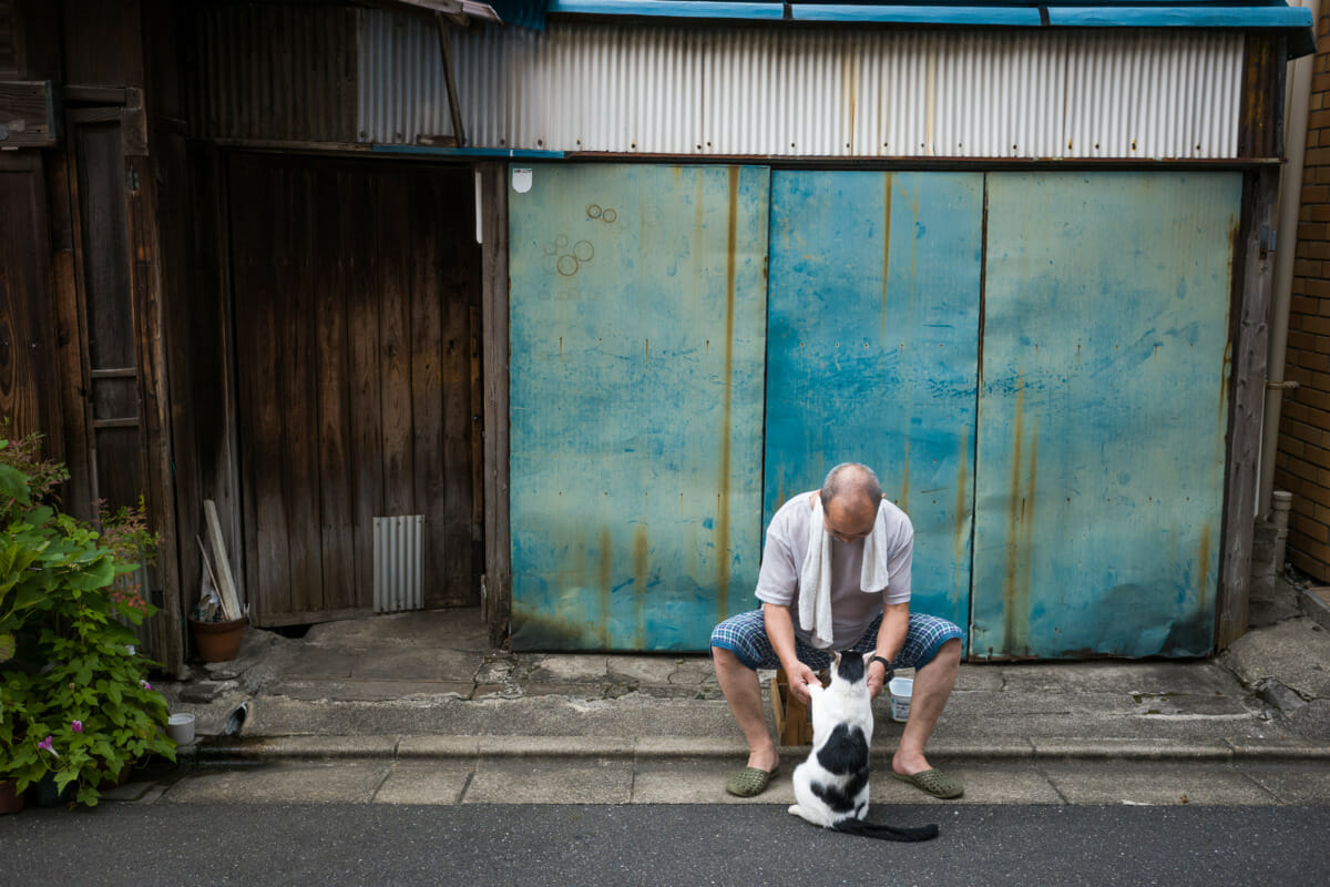 a Japanese man and his cat in an old Tokyo neighbourhood