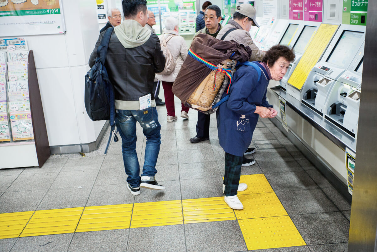 a little old Japanese lady with a very big bag