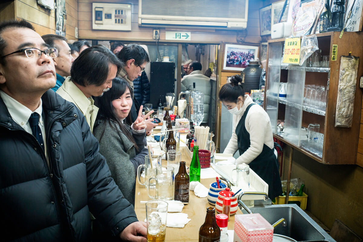 Japanese woman in a jam-packed Tokyo standing bar