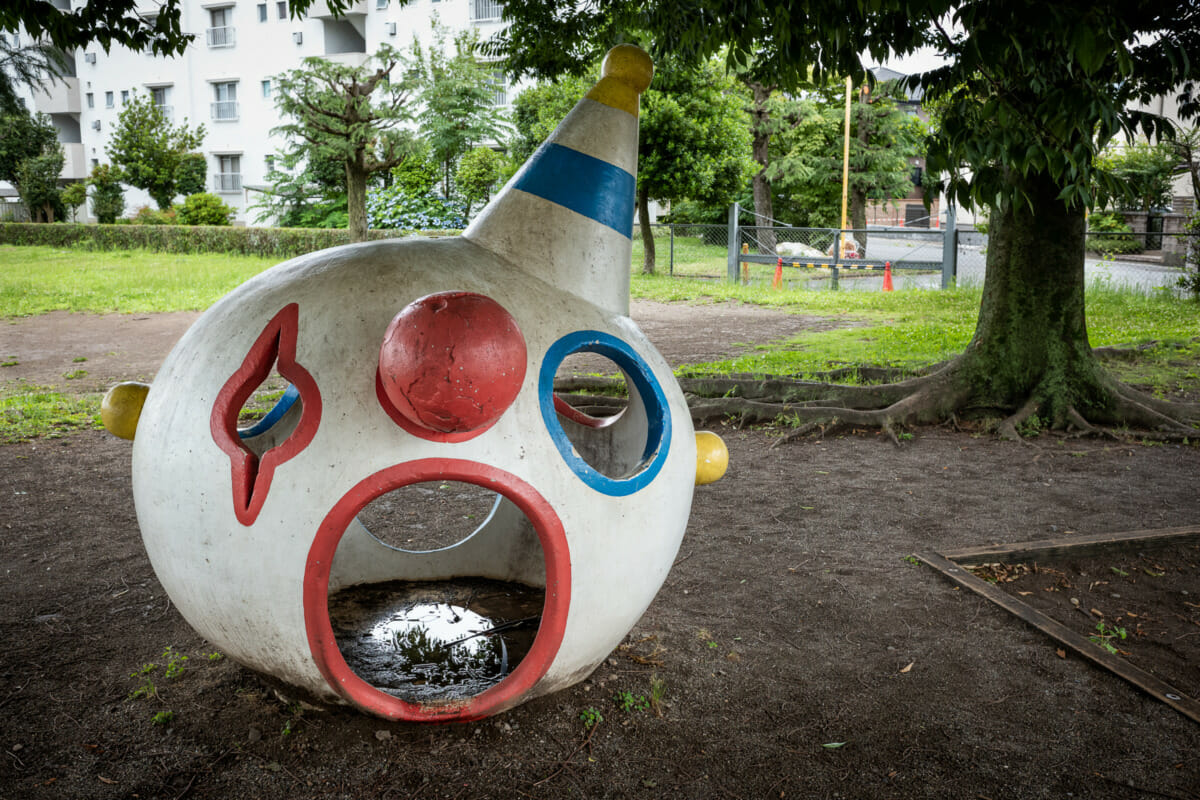 a disturbing concrete clown head in a Japanese playground