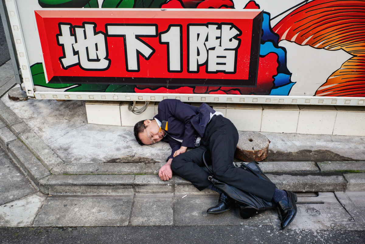 A Japanese salary man drunk and asleep on the street