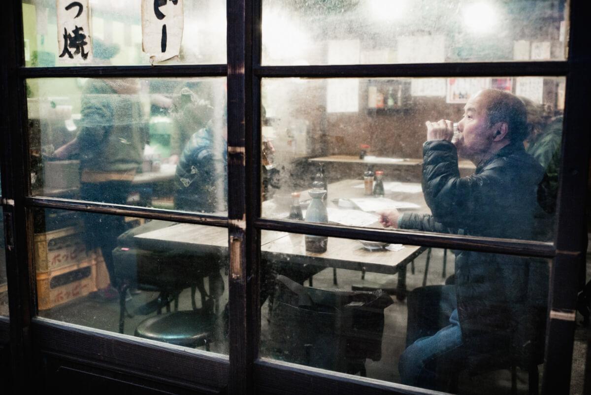 an atmospheric Tokyo bar and a Japanese man drinking sake