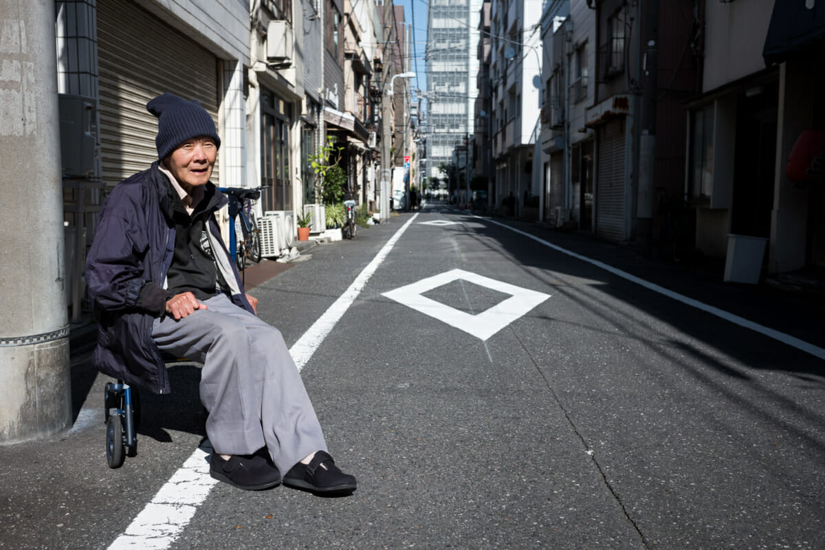 an old Japanese man sat out on a Tokyo side street