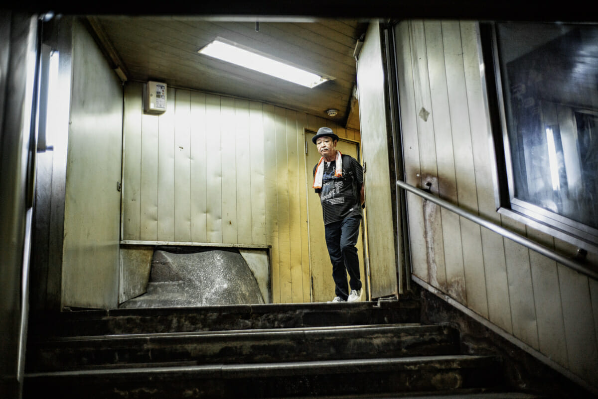 An old man in an old and retro Tokyo subway entrance