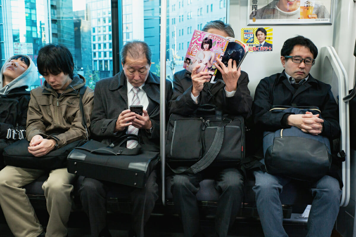 A Japanese salaryman reading adult manga on the morning commute