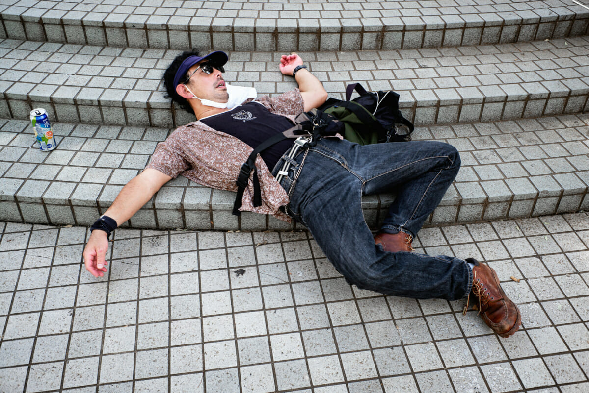 An 80s style Japanese man drunk and asleep on the street