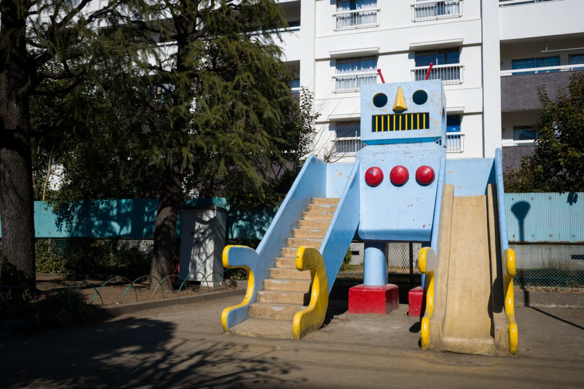 A large and retro concrete robot in an urban Tokyo park