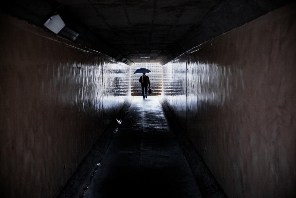 tokyo umbrella man in a dark passageway